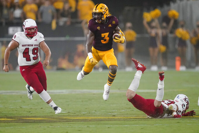 Arizona State running back Rachaad White (3) avoids the tackle of Southern Utah linebacker Trent Whalen (53) as long snapper Chris Kent (49) pursues during the first half of an NCAA college football game, Thursday, Sept. 2, 2021, in Tempe, Ariz. (AP Photo/Matt York)