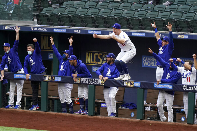 Los Angeles Dodgers celebrate a home run by Justin Turner during the first inning in Game 6 of a baseball National League Championship Series against the Atlanta Braves Saturday, Oct. 17, 2020, in Arlington, Texas. (AP Photo/Tony Gutierrez)