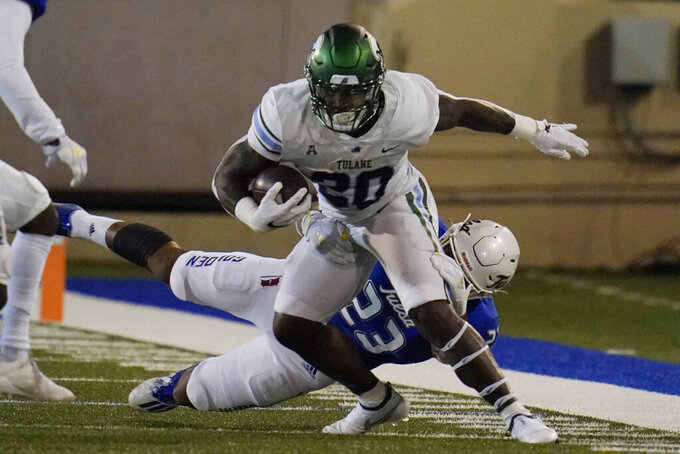 Tulane running back Cameron Carroll (20) is tackled by Tulsa linebacker Zaven Collins (23) during the first half of an NCAA college football game in Tulsa, Okla., Thursday, Nov. 19, 2020. (AP Photo/Sue Ogrocki)