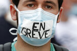 An hospital worker wears a face mask writing « In strike » during a demonstration, Tuesday, June 16, 2020 in Paris. French hospital workers and others are protesting in cities around the country to demand better pay and more investment in France's public hospital system, which is considered among the world's best but struggled to handle a flux of virus patients after years of cost cuts. France has seen nearly 30,000 virus deaths. (AP Photo/Thibault Camus)