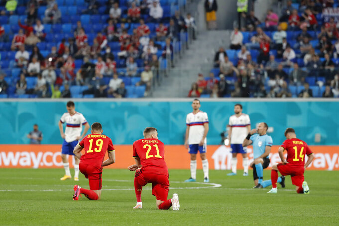 Players of Belgium kneel down prior the start of the Euro 2020 soccer championship group B match between Belgium and Russia at the Saint Petersburg stadium in St. Petersburg, Russia, Saturday, June 12, 2021. (Anatoly Maltsev/Pool via AP)