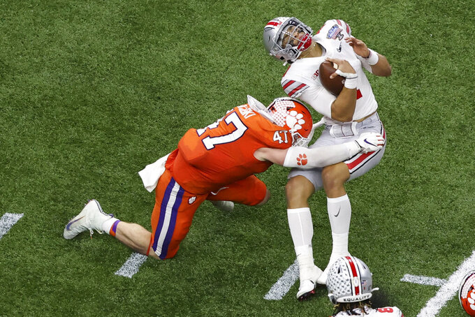 Ohio State quarterback Justin Fields gets hit by Clemson linebacker James Skalski during the first half of the Sugar Bowl NCAA college football game Friday, Jan. 1, 2021, in New Orleans. Skalski was ejected from the game for targeting.(AP Photo/Butch Dill)