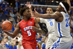 Southern Methodist guard Emmanuel Bandoumel (5) handles the ball against Memphis forward D.J. Jeffries (0) and center Malcolm Dandridge (23) in the first half of an NCAA basketball game Saturday, Jan. 25, 2020, in Memphis, Tenn. (AP Photo/Brandon Dill)