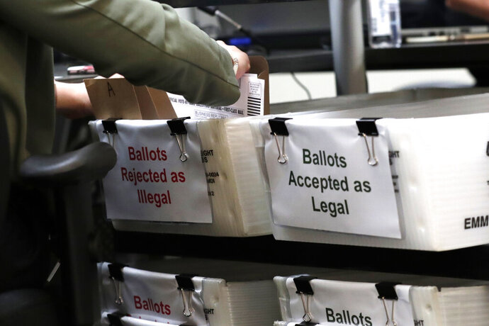 A Miami-Dade County Elections Department employee places a vote-by-mail ballot for the August 18 primary election into a box for rejected ballots as the canvassing board meets at the Miami-Dade County Elections Department, Thursday, July 30, 2020, in Doral, Fla. President Donald Trump is for the first time publicly floating a