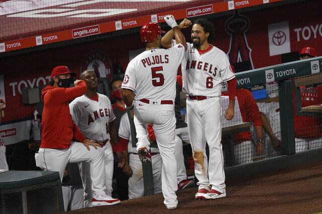 Los Angeles Angels' Albert Pujols (5) celebrates with Anthony Rendon while heading into the dugout after a solo home run during the fifth inning of the team's baseball game against the Seattle Mariners in Anaheim, Calif., Tuesday, July 28, 2020. (AP Photo/Kelvin Kuo)