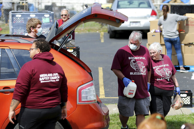 Church members Brian Helton and Donna Covert help load food during a drive-thru food distribution service Saturday, April 4, 2020, in front of Highland Avenue Baptist Church in Elmwood Place, Ohio. At least 800 vehicles passed through, each receiving a pre-packed 40-pound emergency food box with staples like peanut butter, spaghetti, canned fruits, vegetables, oatmeal, and chili, and two gallons of milk, a frozen chicken,18 eggs and produce from the Freestore Foodbank of Cincinnati, according to Jessie Fossenkemper, the community partnership manager. (Kareem Elgazzar/The Cincinnati Enquirer via AP)