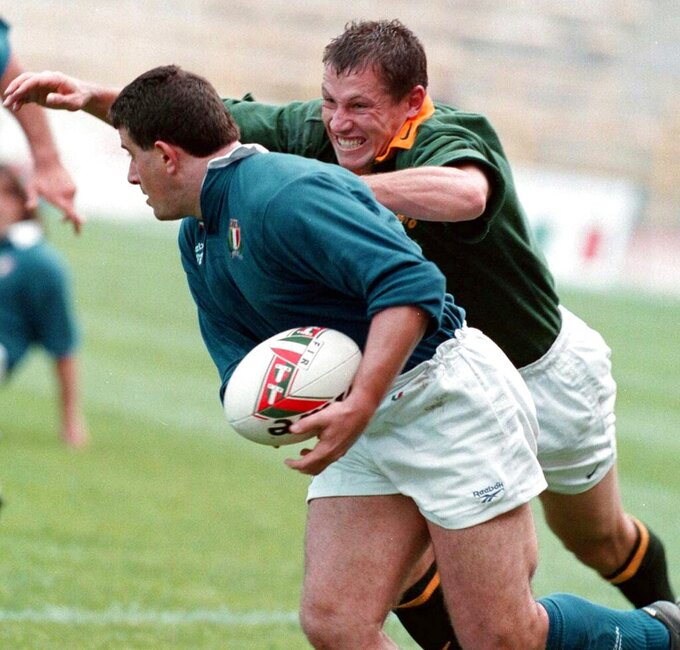 FILE - In this Saturday, Nov, 8, 1997 file photo, Italy's Massimo Cuttitta, left, is challenged by a South Africa's player during a rugby union test match at the Renato Dall'Ara stadium in Bologna, Italy. Massimo Cuttitta, a former captain of Italy's rugby team, has died after contracting the coronavirus. He was 54. Cuttitta had recently been hospitalized in Rome with COVID-19 and died Sunday following complications from the virus, the Six Nations said. (AP Photo/Renato Ferrini, File)
