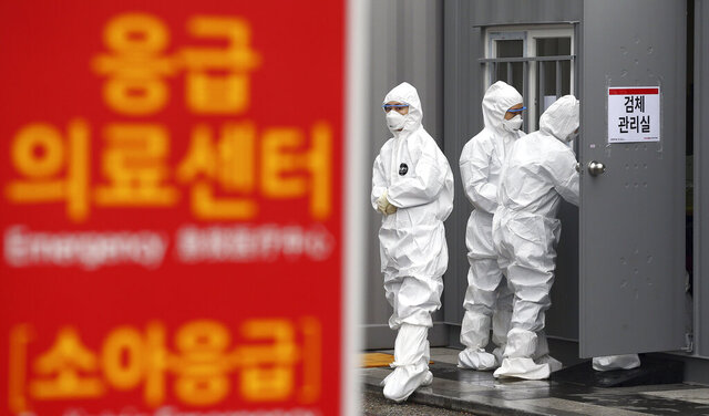 Officials wearing protective attire work to diagnose people with suspected symptoms of the new coronavirus at a hospital in Daegu, South Korea, Wednesday, Feb. 26, 2020. The number of new virus infections in South Korea jumped again Wednesday and the U.S. military reported its first case among its soldiers based in the Asian country, with his case and many others connected to a southeastern city with an illness cluster. A sign reads