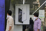 People walk past an image of an iPhone displayed at an Apple store in Ahmedabad, India, Saturday, Aug. 1, 2020. Three contract manufacturers for Apple iPhones and South Korea's Samsung have applied for large-scale electronics manufacturing rights in India under a $6.5 billion incentive scheme announced by the government, Technology Minister Ravi Shankar Praad  said Saturday. (AP Photo/Ajit Solanki)