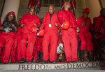 Leader of the Economic Freedom Fighters (EFF) party Julius Malema, center, and his members dance on the steps of parliament after walking out of Parliament at the State of the Nation Address in Cape Town, South Africa, Thursday, Feb. 13, 2020. (Brenton Geach/Pool Photo via AP)