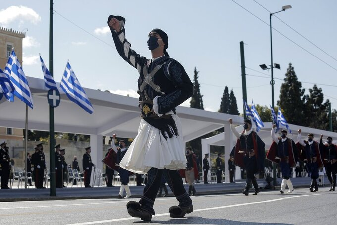 Members of the Greek army march with traditional costumes during a parade in Athens, Thursday, March 25, 2021. Fighter jets flew by the ancient Acropolis and tanks rumbled past parliament in central Athens as Greece's celebrations for the bicentenary of the nation's war of independence culminated in a military parade attended by dignitaries from Britain, France and Russia but no public. (Kostas Tsironis/Pool via AP)