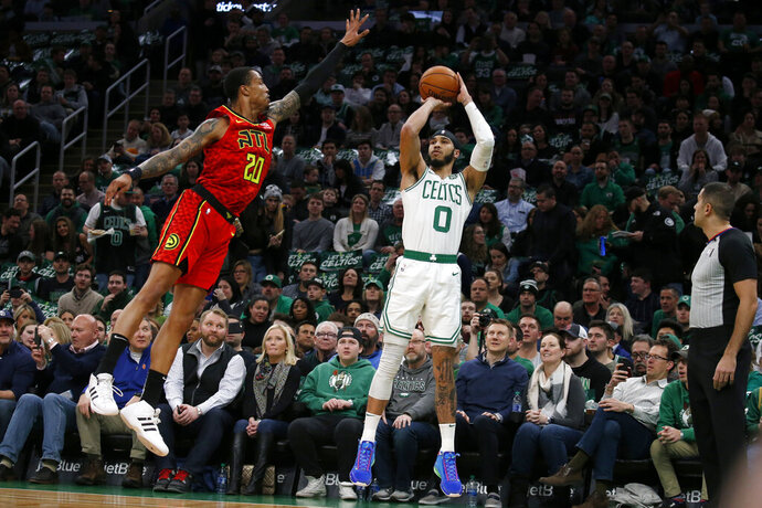 Boston Celtics forward Jayson Tatum (0) shoots a 3-pointer against Atlanta Hawks forward John Collins (20) during the first half of an NBA basketball game Friday, Feb. 7, 2020, in Boston. (AP Photo/Mary Schwalm)