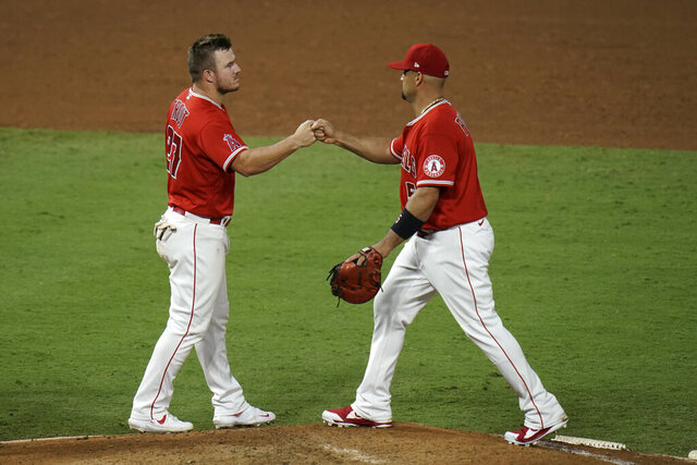 Los Angeles Angels' Albert Pujols, right, and Mike Trout bump fists as they celebrate the team's 7-6 win against the Houston Astros in the second baseball game of a doubleheader Saturday, Sept. 5, 2020, in Anaheim, Calif. (AP Photo/Jae C. Hong)