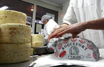 FILE - In this Jan. 22, 2009, file photo, employees work at Carles Roquefort cheese factory in Roquefort, southwestern France. Speaking at China International Import Expo, French President Emmanuel Macron announced an agreement between the European Union and China about the mutual protection of food and alcohol products, to be formally signed on Wednesday. Amid 26 protected French products are the Champagne, wines including those from Bordeaux and Burgundy regions, Cognac liquor and some cheeses like Roquefort. (AP Photo/Bob Edme, File)