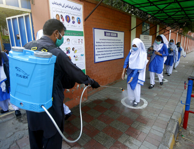 FILE - In this Sept. 15, 2020, file photo, a worker disinfects shoes of a student upon her arrival at a school, in Lahore, Pakistan. The global pandemic and ensuing lockdown have taken their toll on the mental and physical well-being of millions of kids in the Middle East and North Africa, the U.N. children's agency said Friday, Nov. 20, 2020. (AP Photo/K.M. Chaudary, File)