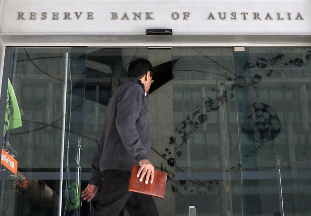 FILE - In this Oct. 1, 2019, file photo, a man walks past the Reserve Bank of Australia in Sydney. Australia's central bank on Tuesday, March 3, 2020 cut its benchmark interest rate by a quarter of a percentage point to a record low of 0.5% in response to the economic shock of the new coronavirus. (AP Photo/Rick Rycroft, File)