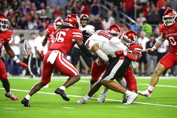 Texas Tech tight end Travis Koontz (15) is tackled my multiple Houston defenders during the second half of an NCAA college football game Saturday, Sept. 4, 2021, in Houston. (AP Photo/Justin Rex)
