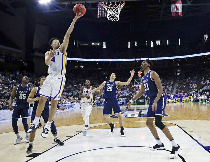 LSU's Skylar Mays (4) goes up for a shot over Yale 's Paul Atkinson (20) and Jordan Bruner (23) during the first half of a first round men's college basketball game in the NCAA Tournament in Jacksonville, Fla., Thursday, March 21, 2019. (AP Photo/John Raoux)