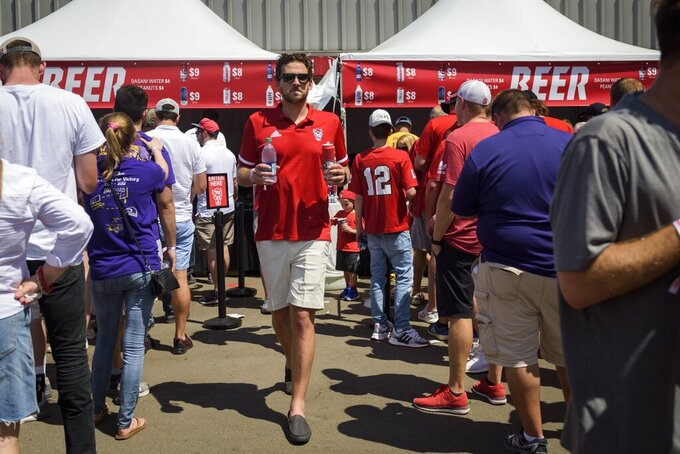 North Carolina State alumni Matthew DiGioia carries a beer during an NCAA college football game between North Carolina State and East Carolina at Carter Finley Stadium in Raleigh, N.C., Saturday, Aug 31, 2019.  There's a growing trend at Atlantic Coast Conference football games: alcohol sales to the general public.  Now everyone can enjoy their beverage of choice at most ACC stadiums, not just boosters and donors.  (Bryan Cereijo/The News & Observer via AP)