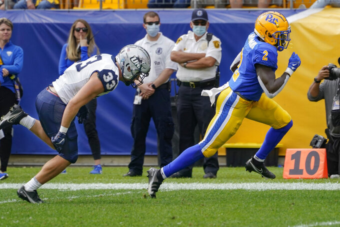 Pittsburgh running back Israel Abanikanda (2) eludes New Hampshire safety Kenny Fazio (33) on his way to a touchdown during the first half of an NCAA college football game, Saturday, Sept. 25, 2021, in Pittsburgh. (AP Photo/Keith Srakocic)