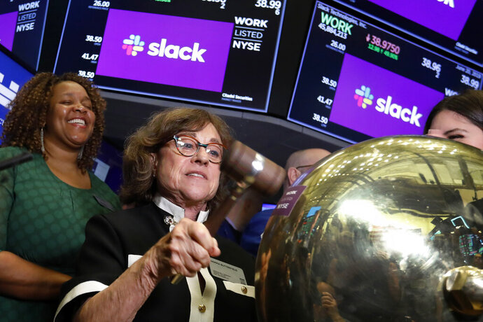 Norma Butterfield, mother of Slack Technologies CEO Stewart Butterfield, rings a ceremonial bell on the floor of the New York Stock Exchange as the Slack IPO begins trading, Thursday, June 20, 2019. (AP Photo/Richard Drew)