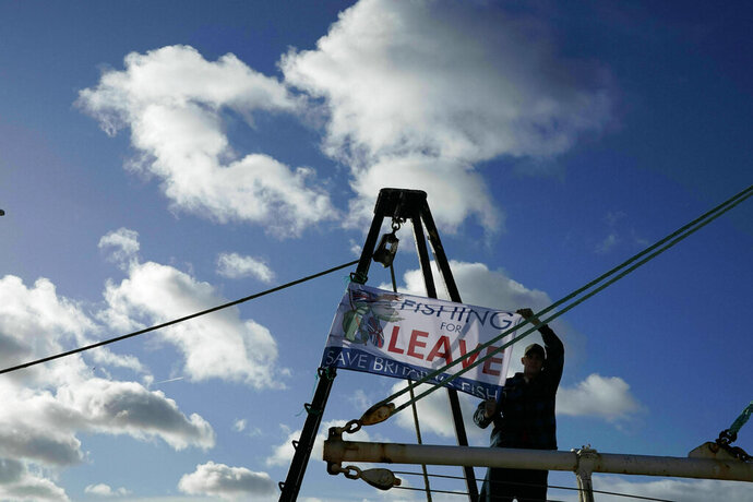 A fisherman joins demonstrators at a pro-Brexit March to Leave protest, at Newcastle Quayside, in Newcastle, England, Friday March 15, 2019. British Prime Minister Theresa May is working to pull off an against-the-odds rescue for her European Union divorce deal, after Parliament voted to postpone Brexit to avert a chaotic U.K. departure in two weeks.  (Owen Humphreys/PA via AP)