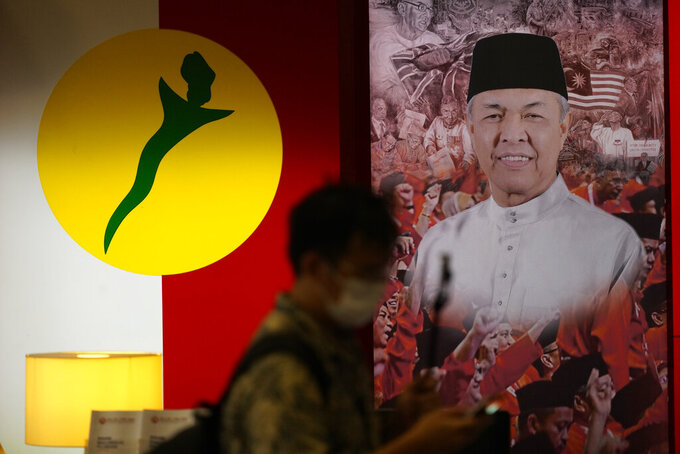 A man walks in front of a poster of UMNO ( United Malays National Organisation) President Ahmad Zahid at UMNO headquarter in Kuala Lumpur, Malaysia, Monday, Oct. 26, 2020. A key ally has reaffirmed support for Malaysian Prime Minister Muhyiddin Yassin's government, offering him a respite after his failed bid to declare a coronavirus emergency,  but his political survival still hangs in the balance. The UMNO, the biggest party in the unelected governing coalition was angry at being sidelined amid rivalry with Muhyiddin's own Malay party.   (AP Photo/Vincent Thian)