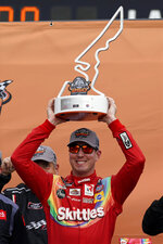 Kyle Busch raises the trophy in Victory Lane after winning the NASCAR Xfinity Series auto race at the Circuit of the Americas in Austin, Texas, Saturday, May 22, 2021. (AP Photo/Chuck Burton)
