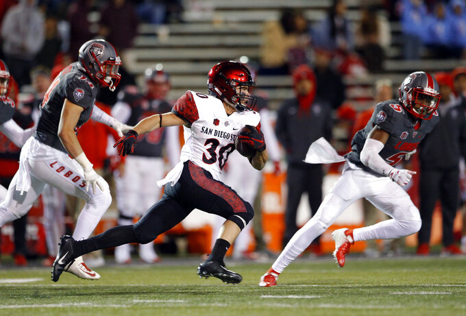 San Diego State cornerback Garrett Binkley (30) runs for yardage on a kickoff return followed by New Mexico safeties Michael Sewell (5) and Gabe Ortega (14) during the second half of an NCAA college football game in Albuquerque, N.M., Saturday, Nov. 3, 2018. San Diego State won 31-23. (AP Photo/Andres Leighton)