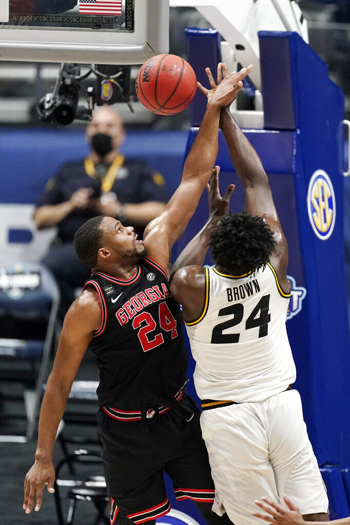 FILE -  Missouri's Kobe Brown, right, drives against Georgia's P.J. Horne, left, in the first half of an NCAA college basketball game in the Southeastern Conference Tournament in Nashville, Tenn., in this Thursday, March 11, 2021, file photo. Senior forward P.J. Horne, Georgia's only returning starter, will miss the 2021-22 season after suffering a knee injury in practice. Georgia coach Tom Crean said Wednesday, Oct. 20, 2021, on his Twitter account Horne had season-ending surgery on his right knee last weekend. (AP Photo/Mark Humphrey, File)