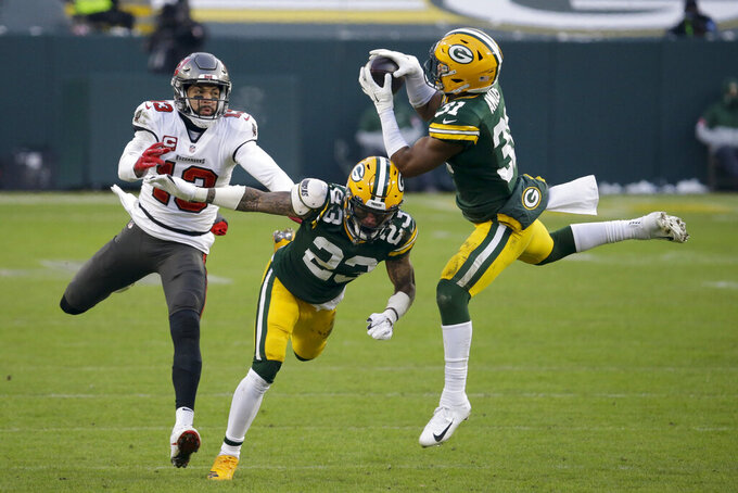 Green Bay Packers' Adrian Amos (31) intercepts a pass intended for Tampa Bay Buccaneers' Mike Evans (13) as Jaire Alexander (23) defends during the second half of the NFC championship NFL football game in Green Bay, Wis., Sunday, Jan. 24, 2021. (AP Photo/Mike Roemer)