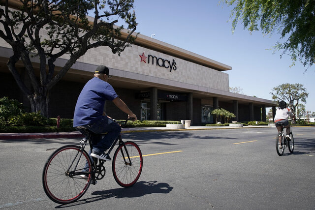 FILE - In this March 30, 2020 file photo, bicyclists pass in front of a closed Macy's department store in Santa Ana, Calif. Macy's warned Thursday, May 21 that it could lose more than a $1 billion during its first quarter after the coronavirus pandemic paralyzed retail operations worldwide. (AP Photo/Chris Carlson)
