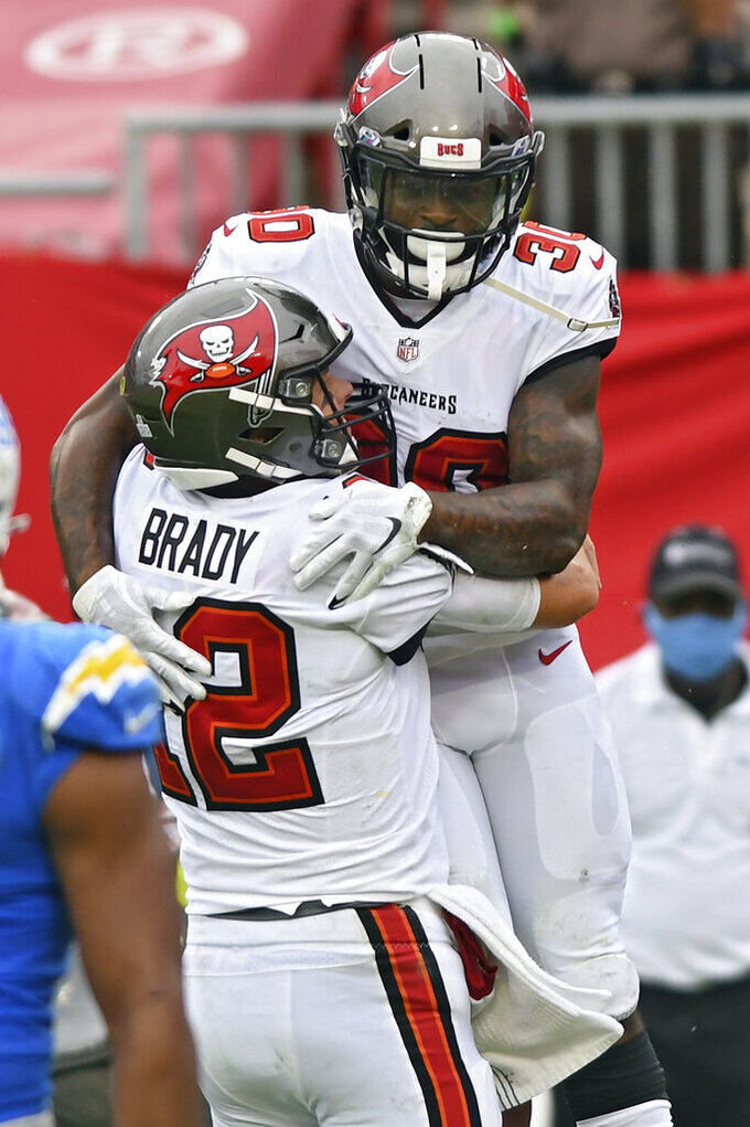 Tampa Bay Buccaneers running back Ke'Shawn Vaughn (30) celebrates with quarterback Tom Brady (12) after scoring against the Los Angeles Chargers during the second half of an NFL football game Sunday, Oct. 4, 2020, in Tampa, Fla. (AP Photo/Jason Behnken)