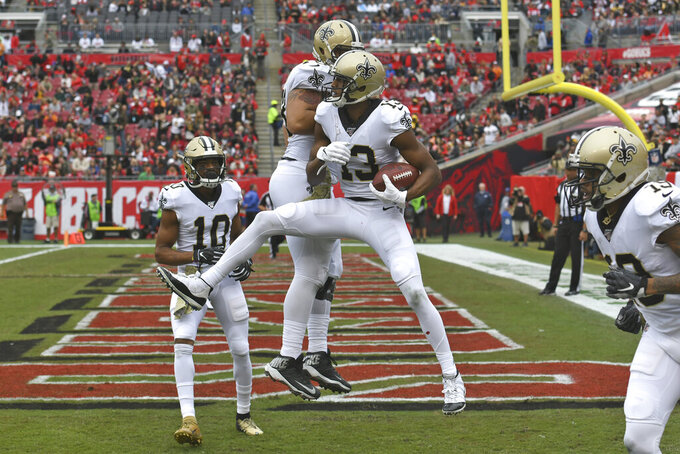 New Orleans Saints wide receiver Michael Thomas (13) celebrates his 16-yard touchdown reception with wide receiver Tre'Quan Smith (10) and center Erik McCoy (78) during the first half of an NFL football game Sunday, Nov. 17, 2019, in Tampa, Fla. (AP Photo/Jason Behnken)