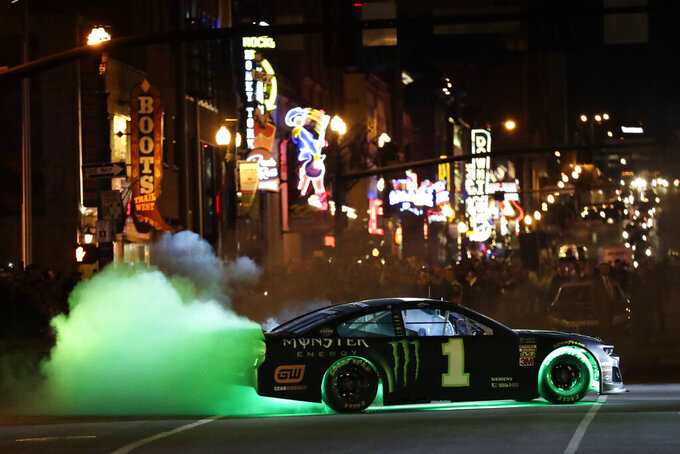 NASCAR driver Kurt Busch does a burnout in the Burnouts on Broadway competition Wednesday, Dec. 4, 2019, during NASCAR Champion's Week in Nashville, Tenn. (AP Photo/Mark Humphrey)