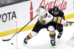 Vegas Golden Knights left wing William Carrier (28) controls the puck in front of Los Angeles Kings center Blake Lizotte during the second period of an NHL hockey game Friday, March 19, 2021, in Los Angeles. (AP Photo/Marcio Jose Sanchez)