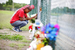 Christal McLemore prays at a makeshift memorial at the spot where Miracle Crook, 3, and Tony Crook, 2, walked down to Mingo Creek at the Shoreline Apartments Wednesday, May 27, 2020. McLemore's grandaughter is the oldest sibling of the missing two children. (Mike Simons/Tulsa World via AP)