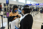 Airport staff takes a passenger's temperature amid the COVID-19 pandemic in Cancun, Mexico, Saturday, June 13, 2020. In Quintana Roo state, where Cancun is located, tourism is the only industry there is, and Cancun is the only major Mexican resort to reopen so far. (AP Photo/Victor Ruiz)
