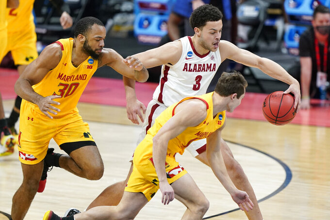 Alabama's Alex Reese (3) tries to protect the ball from Maryland's Galin Smith (30) and Reese Mona, front, during the first half of a college basketball game in the second round of the NCAA tournament at Bankers Life Fieldhouse in Indianapolis Monday, March 22, 2021. (AP Photo/Mark Humphrey)