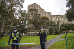 Police guard access to housing commission apartments under lockdown in Melbourne, Australia, on Monday, July 6, 2020. The hard-hit Australian state of Victoria recorded two deaths and its highest-ever daily increase in coronavirus cases on Monday as authorities prepare to close its border with New South Wales. (AP Photo/Andy Brownbill)