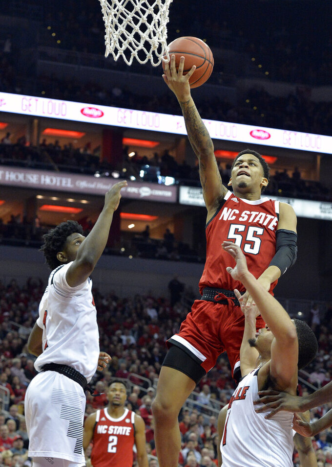 North Carolina State guard Blake Harris (55) goes in for a layup over Louisville guard Darius Perry (2) and guard Christen Cunningham (1) during the first half of an NCAA college basketball game in Louisville, Ky., Thursday, Jan. 24, 2019. (AP Photo/Timothy D. Easley)