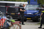 A forensics expert with a backpack full of cameras maps the area where a lawyer who represented a key witness in a major Dutch organized crime trial was gunned down in Amsterdam, in Amsterdam, Netherlands, Wednesday, Sept. 18, 2019. Police said that 44-year-old lawyer Derk Wiersum was fatally shot Tuesday morning by a man who fled on foot and was still being hunted. (AP Photo/Peter Dejong)