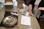 Mendy McNulty gathers test swabs together for shipment after doing a coronavirus test on her family Tuesday,  July 28, 2020, in their home in Mount Juliet, Tenn. Evidence from the U.S., China and Europe shows children are less likely to become infected with the virus than adults and to become seriously ill when they do get sick. There is also data suggesting that young children don't transmit COVID-19 very often but that kids aged 10 and up may spread the virus just as easily as adults. The new study aims to find more solid proof. (AP Photo/Mark Humphrey)