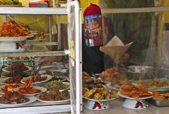 An employee serves customers from behind a plastic sheet installed as a precaution against the new coronavirus at a street food stall in Jakarta, Indonesia, Friday, July 24, 2020. (AP Photo/Tatan Syuflana)