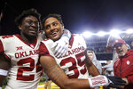Oklahoma linebacker Brian Asamoah (24) celebrates with linebacker Nik Bonitto (35) after Bonitto got an interception that secured a 34-31 win over Baylor in an NCAA college football game, Saturday, Nov. 16, 2019, in Waco, Texas. (Ian Maule/Tulsa World via AP)