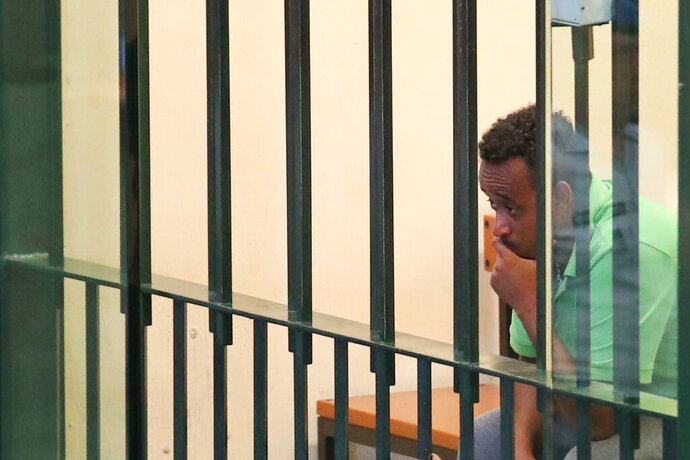 Medhanie Tesfamariam Behre, an Eritrean man arrested and tried as a migrant smuggler, sits behind the bars during a trial inside the Ucciardone bunker hall in the Sicilian town of Palermo, Italy, Friday, July 12, 2019. A court in Palermo, Sicily, ruled on Friday that the wrong Eritrean man was arrested and tried as a migrant smuggling kingpin and ordered him released from jail, to the jubilation of international supporters who had championed for years the defendant's claim of mistaken identity. (Igor Petty/ANSA via AP)