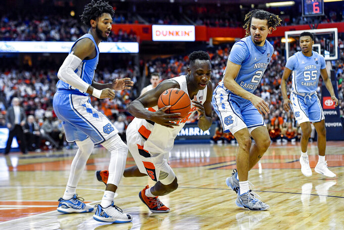Syracuse forward Bourama Sidibe, center, goes to the ground with the ball between North Carolina guard Leaky Black, left, and guard Cole Anthony during the second half of an NCAA college basketball game in Syracuse, N.Y., Saturday, Feb. 29, 2020. North Carolina defeated Syracuse 92-79. (AP Photo/Adrian Kraus)