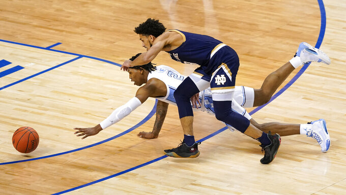 North Carolina guard Andrew Platek (3) and Notre Dame guard Trey Wertz, right, dive for the ball during the first half of an NCAA college basketball game in the second round of the Atlantic Coast Conference tournament in Greensboro, N.C., Wednesday, March 10, 2021. (AP Photo/Gerry Broome)