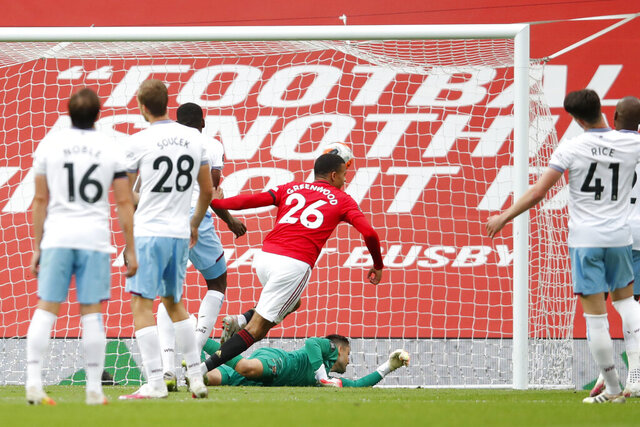 Manchester United's Mason Greenwood scores his side's opening goal during the English Premier League soccer match between Manchester United and West Ham at the Old Trafford stadium in Manchester, England, Wednesday, July 22, 2020. (Clive Brunskill/Pool via AP)