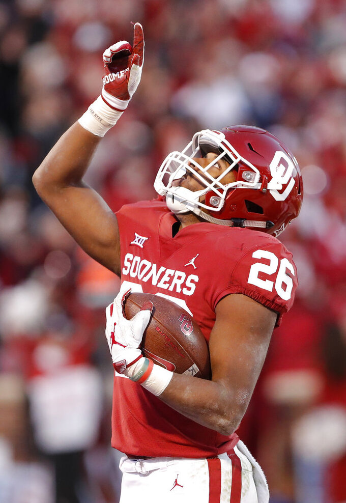 Oklahoma running back Kennedy Brooks (26) reacts after making a touchdown against Oklahoma State in the second half of an NCAA college football game in Norman, Okla., Saturday, Nov. 10, 2018. Oklahoma won 48-47. (AP Photo/Alonzo Adams)